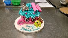 A carved fondant covered Shopkins cake complete with tiara, bow, sprinkles, and tiny fondant friends.