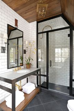 black, white and wood (love the contrast of materials - metal frame, wood beams on the ceiling, porcelain subway tiles. And the floor looks like stone or concrete.)