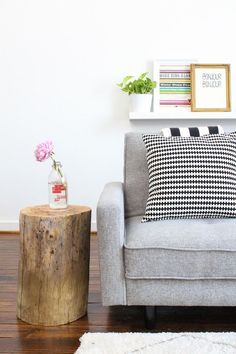 Gray couch, black and white striped pillows, pops of color in prints, greenery, and flower. ❋
