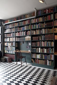Floor-to-ceiling bookshelves with a built-in desk and checkerboard floor.