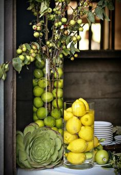 Tall vase with limes and leaves, short vase with lemons, leafy vegetable, and apple.