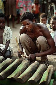 A Malawi man playing a xylophone. BelAfrique your personal travel planner - www.BelAfrique.com