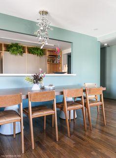 Sala de jantar e cozinha são integradas por uma grande janela.