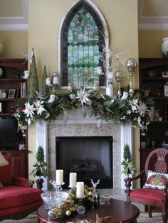 Mantel vignette. Green garland with white poinsettias, wildlife, cone trees, silver ornaments on candlesticks