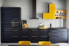 Fitted IKEA kitchen with cabinets in wood effect black and high-gloss yellow.