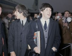 """The Beatles arrive at London Airport, England, February 22, 1964, after their visit to the United States. In the foreground is Paul McCartney, carrying record albums under his arm (including """"Um Um Um Um Um Um - The Best of Major Lance""""), and George Harrison, left, talking to John Lennon."""