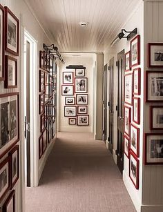 Upstairs hallway - walls covered with red frames and picture lighting - Steven Gambrel