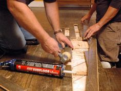 Josh temple uses a mallet to remove the damaged hardwood floor and new adhesive to attach better flooring in this disaster house.