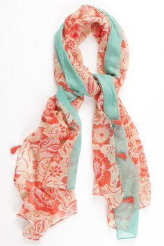 """Get your look ready for summer with the Vine Grove Floral Scarf! This lightweight scarf features a large allover floral print with a contrasting border and tassels along the edge. br><br>    -70"""" length x 31"""" width<br>  -Imported<br>"""