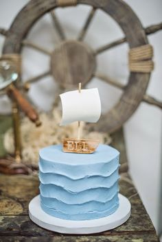 Love this nautical theme cake with blue wave like icing and cute sailboat topper. Source: frostedpetticoatblog.com #cakes #beachwedding #nauticaltheme #caketopper