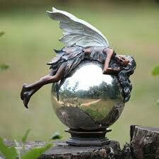 Fairy asleep on globe