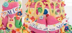 A detailed photograph of wedding cake that say 'all you need is love' during a colorful and fun wedding in Boston, Massachusetts Gina Brocker Photography