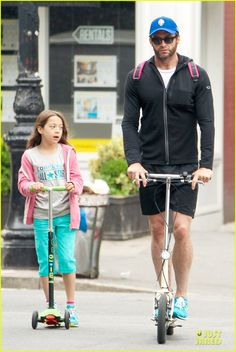 Hugh Jackman rides his scooter while taking his daughter Ava to school on June 10, 2013