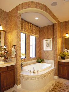 A large tub is nestled in the corner of this luxurious, traditional bathroom. Elegant tile continues the color palette from the wallpaper with a decorative border.
