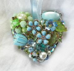 Add romantic beauty to anything you wish to hang this from. This is a heart-shaped mirror embellished with bits and pieces of vintage jewelry.
