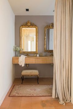 El contraste nuevo/viejo. El mueble de roble del baño, diseño de Growart, es súper actual y contrasta con el look clásico de los espejos antiguos y dorados, la banqueta de herencia familiar, tapizada con terciopelo, y las griferías retro también doradas.