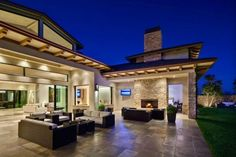 Luxury Spanish Style Hacienda In MariSol Malibu ues modern outdoor seating in this patio seating area adjacent to a stacked stone fireplace...