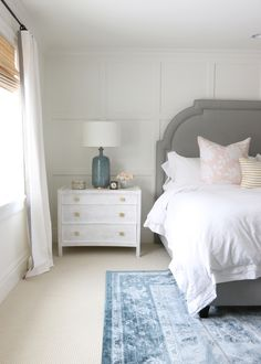 custom grey headboard + white nightstands with matte brass hardware + blue rug and lamps | master bedroom design