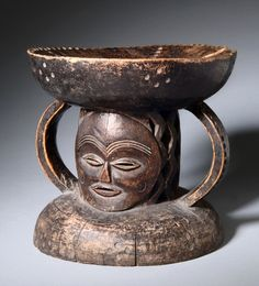 Africa | Stool from the Ovimbundu people of Angola | Wood, with blackish brown patina.  Both sides have been carved with nearly identical faces.