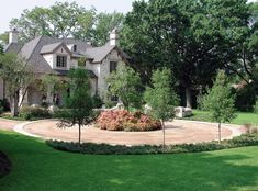 Large circular driveway made of decomposed granite with small garden in the center.
