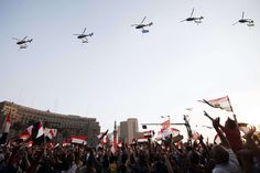 """Egyptian people wave the national flag as army helicopters fly above Egypt's landmark Tahrir square on July 4, 2013. Egypt's Muslim Brotherhood, from which ousted president Mohamed Morsi hails, denounced a new """"police state"""" after the arrest of Islamist leaders and the closure of satellite channels. AFP PHOTO/GIANLUIGI GUERCIA"""