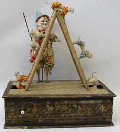 1800's Clown and Dog Act German Musical Automaton. As you turn the hand-crank, the music plays and the poodles climb over the top of the ladder. The clown moves his head back and forth and moves his arm back and forth with the wand.