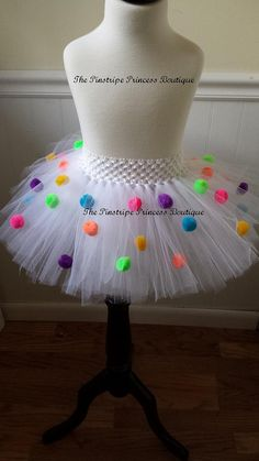 A super cute tutu that is perfect for birthday parties,photo shoots and lots more. Its made with white tulle with multi colored pompoms.  If