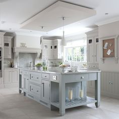 love the dropped ceiling, the legs on the ends of the island, the white and light blue color palette and the marble tile. In other words, I love it all.
