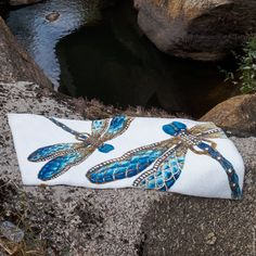 Visit DeWoolfsonLinens.com Felista Bath Rug by Abyss and Habidecor carefully portrays the dragonfly's intricate beauty. Here, a pair are vividly resting upon a lush background of white. In blue and brown hues with golden accents, Felista is going to make a bold statement in any room.  1 colorway 1 size Custom, non-returnable items Please allow 3 to 4 weeks for delivery Made in Portugal For washing instructions, click here.  by Habidecor European Bath Rugs Bath Rugs, Lush, Cuff Bracelets, Portugal, Delivery, Pairs, Brown, Beauty, Cosmetology