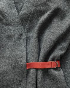 Borrow a trick from wrap dresses to feminize a man's V-neck. Remove buttons. Sew a D ring to the end of a 6-inch piece of knit tape. Stitch other end just inside the sweater, below second buttonhole (here, it's on the left side). Slide D ring onto a 2-foot piece of tape (back of belt), and sew 1 end to left-hand side seam (at same height as short piece). Sew an 8-inch piece of tape to inside of left seam (at same height) and an 8-inch piece at the inside edge of the placket (right side). To…