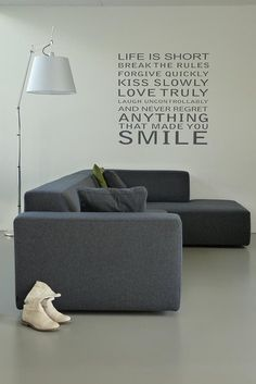 Modern Dutch livingroom: grey loungesofa, white walls (with some wise words) and a grey concrete-look floor.