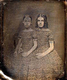 Two young sisters sport identical dresses, but not hairstyles in this elegant Victorian image, c. mid-19th C.