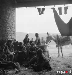 Lors de la campagne de Tunisie, au moment de la réorganisation des troupes du XIXe corps d'armée français et de son repositionnement durant le mois de mars 1943, un groupe de soldats se restaure et se repose dans un secteur de la vallée de l'oued el-Kebir. Date : Mars 1943