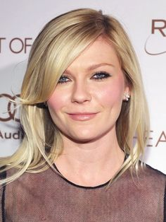 """Don't be intimidated by the thought of bangs—they don't always accentuate a round face. Kirsten Dunst's sweeping fringe, which she matched with a deep side part and a shoulder-length cut, actually thins her face. """"The longest bit of the bang hits midlip, but when you blow it dry and sweep it over, it grazes the cheekbones and defines them really nicely,"""" Lecompte says. He suggests running a texturizer (we love Garnier Fructis Style Pure Clean Finishing Paste) over strands for control."""