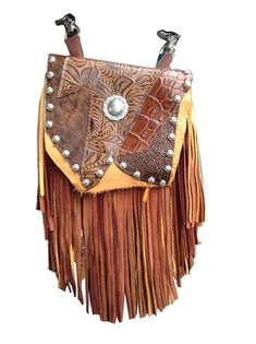 "SILVER FLOWER MARTY - super soft, made of brown deerskin with a 7"" brown and gold deerskin fringe. The floral centerpiece draws the eye, and is surrounded by a multi-textured overlay with hair-on-hide and different kinds of printed leather. Silver metal studs adorn the flap. Wear bag clipped to belt loops for hands-free carrying of your essentials. Interior includes a leather strap. Add the strap when you want a completely different look."