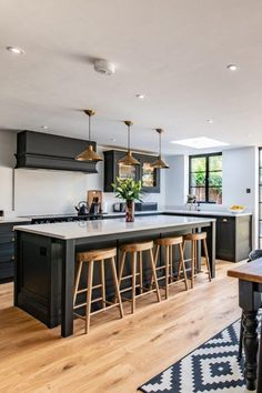 This open plan kitchen features stunning black cabinetry and a large kitchen island. The white quartz worktops and light walls keep the space from looking very dark and the natural elements of wood from the flooring and bar stools soften the design. Open Plan Kitchen Dining Living, Open Plan Kitchen Diner, Living Room Kitchen, Large Open Plan Kitchens, Barn Kitchen, Open Plan Living, Kitchen Room Design, Modern Kitchen Design, Interior Design Kitchen