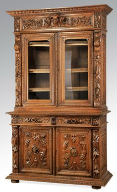 French two part bookcase, 19th century, executed in oak, the pediment carved with a lamb's tongue border above a relief carved entablature centering S scrolls flanked by acanthus flourishes, surmounting pilasters carved with floral decoration flanking the glass front cabinets with gadrooned borders, opening to reveal one shelf, above two drawers carved in relief, surmounting the panel doors carved with central lion's masks, the whole resting on demi lune feet