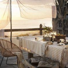 Une salle à manger estivale avec un linge de table aux teintes claires, un coussin Summer et un plaid Summer déposé sur le fauteuil en osier