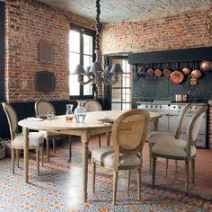 cocina rústica, con frente de pizarra y mesa de comedor clásica, paredes de ladrillo visto