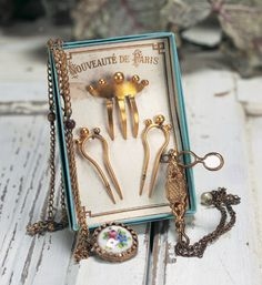 "French Accessories for Bebes or Poupees Includes gold-plated hinged lorgnette with hanging chain, watch with enamel back and extended chain, and a superb set of decorative gold-plated doll combs still arranged on their original ""Nouveautes de Paris"" card. Excellent condition. French,circa 1880. Realized Price: 750 Theriault's Antique Doll Auctions"