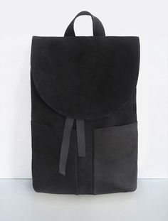 Mumandco backpack, with various geometric shapes (a semicurcular top, rectangular pockets) and shades of black.