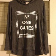 """No One Cares Paris""""Grey&White Long Sleeve Top NWT. Grey &White long sleeve/ draw strap hooded top. White colored print """"No One Cares Paris"""" High Low Hem. Size:large (fits more like a s/m) Tops"""