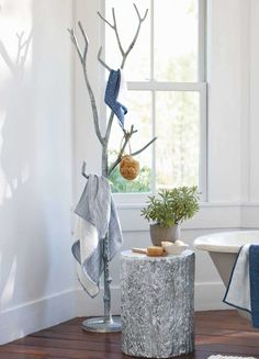 I would love this as a towel bar in my bath. I am always looking for unique ways to hang towels in my bath. Towel bars can be boring. But this tree branch is such a great idea. Why didn't I think of it. Actually. You could make one. I would just make sure you use water resistant paint, anchor the branch well, and ensure that it will rest tightly between floor and ceiling.
