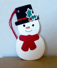 snowman with top hat, scarf, and holly leaves.