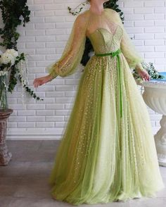 Details - Green color - Sparkling tulle fabric - Green velvet belt - A-line gown with waist definition and long sleeves - For special occasions Tulle Prom Dress, Ball Gown Dresses, Grad Dresses, Gold Dress, Pretty Dresses, Beautiful Dresses, Prom Dresses Long With Sleeves, Green Long Sleeve Dress, Dress Shapes