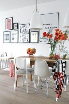 chaise en plastique blanc, sol en parquet beige, lustre blanc, peintures murales décoratives