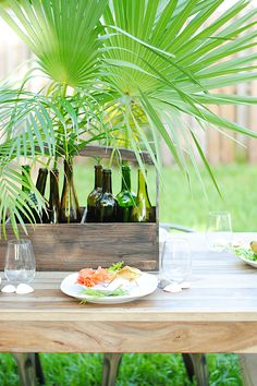 This wooden caddy from HomeGoods hosts recycled wine bottles with large tropical leaves for a quick and beautiful centerpiece.
