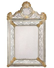 antiqued Venetian mirror framed in hand-etched glass with gold highlights, trimmed with ribbons and rosettes
