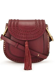 Shop now. Chloé Hudson Small Shoulder Bag. This small and perfectly formed calfskin suede Hudson saddle bag by Chloé comes in a rich shade of claret and features brass coloured stud and braided leather details. Finished with a dainty tassel at the snap fastening and a cross-body strap, this versatile bag hides an extra compartment inside the roomy interior as well as an additional front pocket.