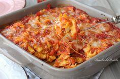 Tortellini al forno con pomodoro e mozzarella. Una variante filante, molto più celere e non meno gustosa della classica pasta al forno con besciamella.